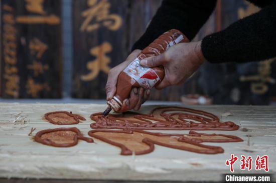 余平华在用特殊的泥沙勾勒文字。 瞿宏伦 摄