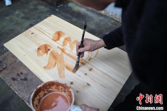 """余平华在木板上书写""""福""""字。 瞿宏伦 摄"""