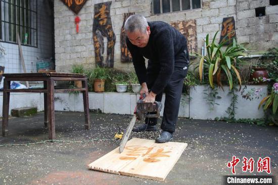 余平华在切割木板。 瞿宏伦 摄
