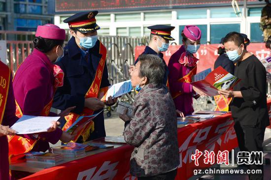 贵阳客运段青年志愿者给旅客发放铁路旅行消防安全常识手册。沈向全 摄