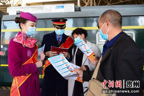 K496次贵阳站台上,志愿者向旅客们发放铁路旅行消防安全宣传册。沈向全 摄