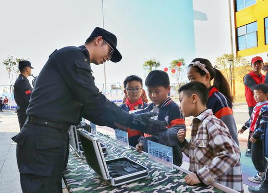 民警向小朋友介绍警用装备。 王荐斐 摄