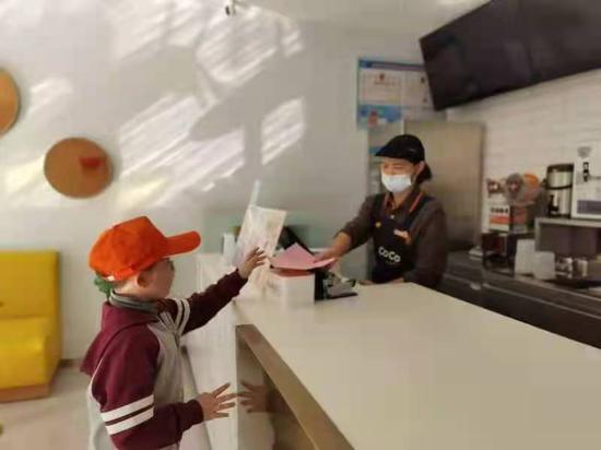 小学生们向沿街店铺发放垃圾分类宣传资料。 金华开发区垃圾分类办提供