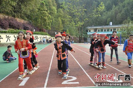 资料图:近年来,金秀瑶族自治县注重将民族团结理念融入教学课程、校园环境和课外活动。图为不同瑶族支系的学生身着瑶服开展课外拓展活动。