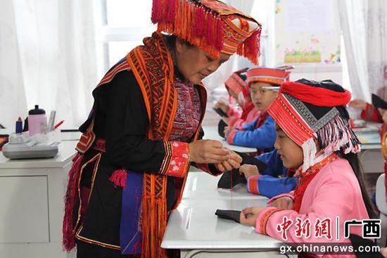 为传承瑶族刺绣文化,金秀将瑶族刺绣课程纳入小学教育兴趣课程,弘扬少数民族文化。图为老师为学生教授瑶族刺绣针法。