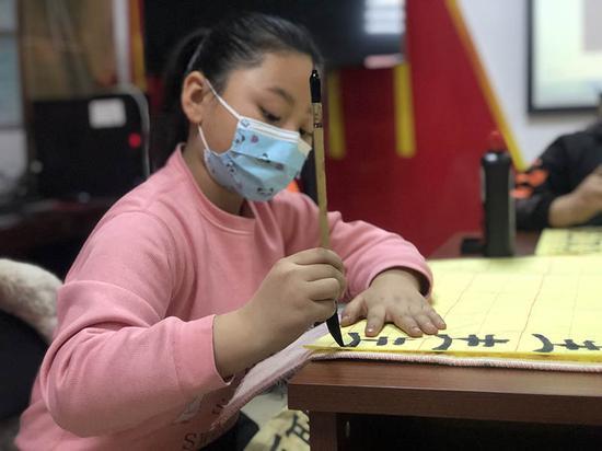 小学生杨岚一笔一划,认真书写。