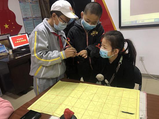 马小程、李向荣同学给余静伊小朋友讲解握笔姿势。
