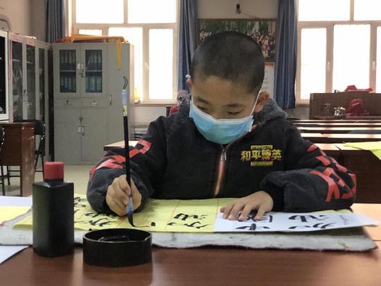 """小学生李向荣书写""""加油中国""""。"""