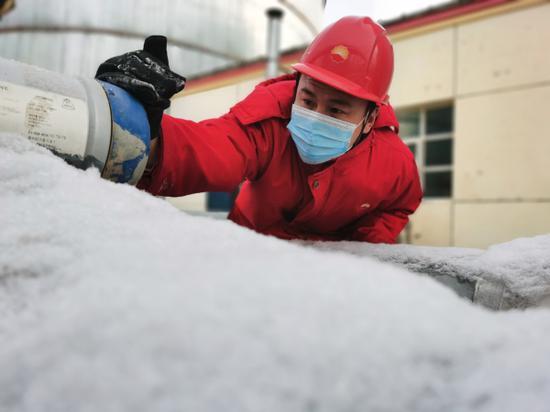 新疆油田公司风城油田一号稠油联合处理站员工在查看雪后的水区流量计是否正常。郑娟摄
