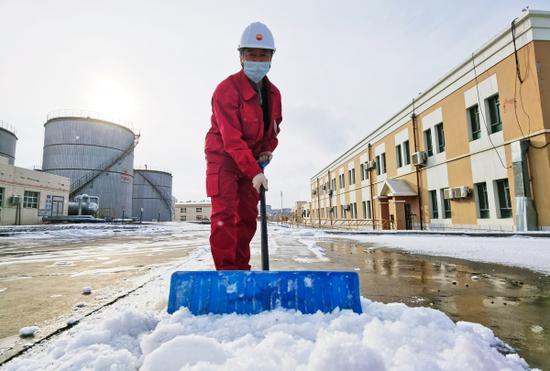 新疆油田公司风城油田一号稠油联合处理站员工在清扫巡检道路上的积雪。郑娟摄