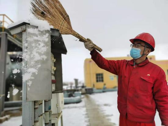 新疆油田公司风城油田采油三站员工在清理积雪。沈婕摄