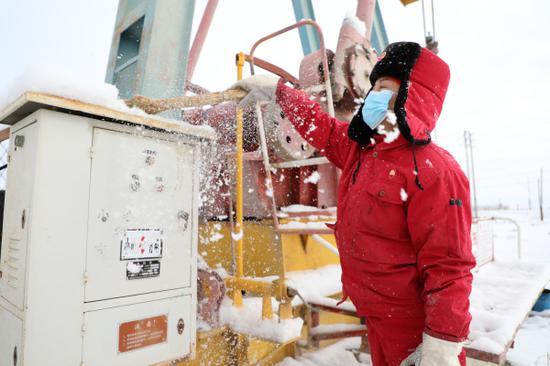 新疆油田公司采油二厂员工对抽油机上的积雪进行清扫,确保雪天设备设施正常运行。刘奕汝摄