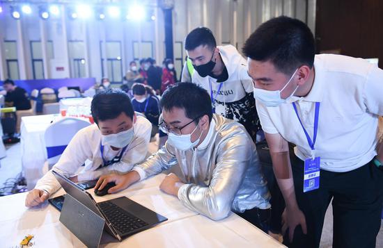 多位参赛者在现场优化机器人程序。王刚 摄