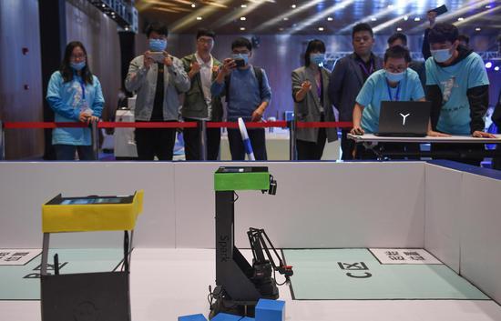 两台机器人进行夺宝奇兵自动对抗赛吸引参观者。王刚 摄