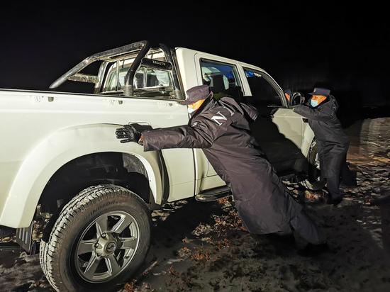 1月19日晚,新疆阿勒泰边境管理支队阿热勒边境派出所民警正在帮助滑下路基车辆脱困。