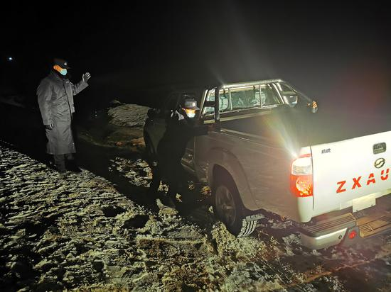 11月19日晚,新疆阿勒泰边境管理支队阿热勒边境派出所民警正在帮助滑下路基车辆脱困。 (