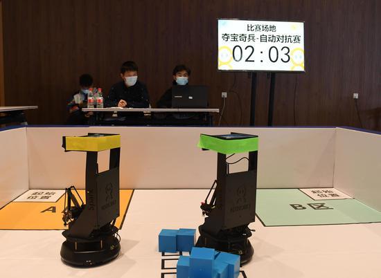 两台机器人在参加夺宝奇兵自动对抗赛。王刚 摄