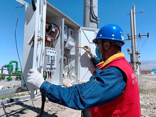 国网哈密供电公司工作人员给客户安装智能电表。冯洋 摄