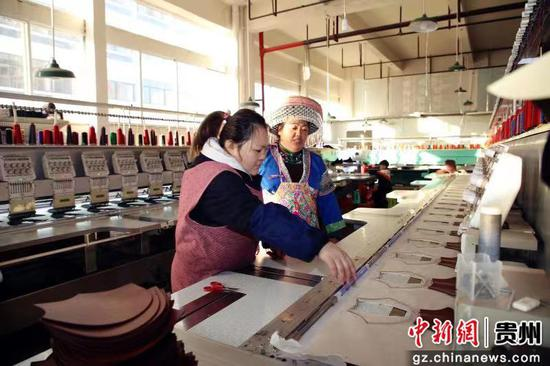 圖為王信梅(右一)向公司職工指導苗繡製作技藝