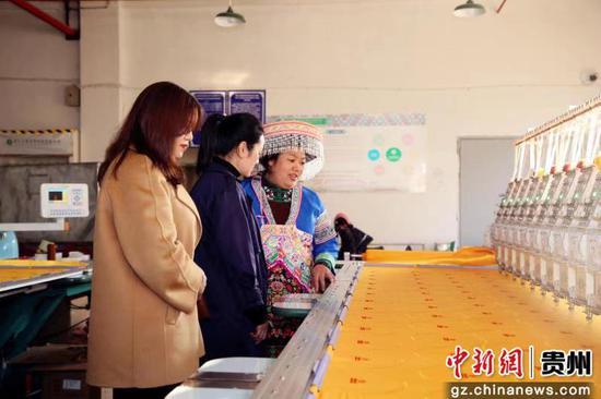 圖為王信梅(右一)向客商介紹苗藥產品制作流程 。