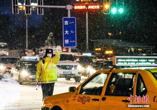 乌鲁木齐持续降雪道路湿滑 交警雪中坚守岗位