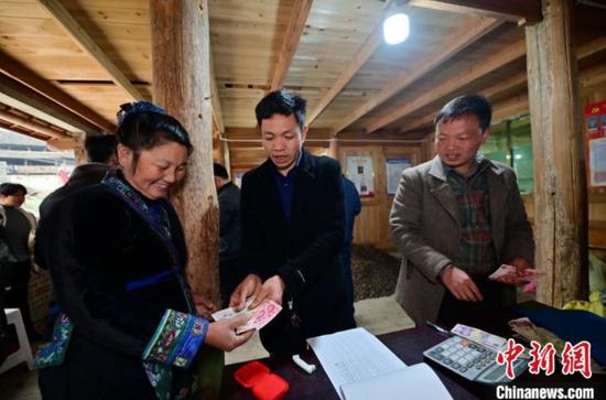 11月27日,在貴州省從江縣斗里鎮臺里村,合作社工作人員在兌現銷售的油茶籽現金?!堑萝?攝