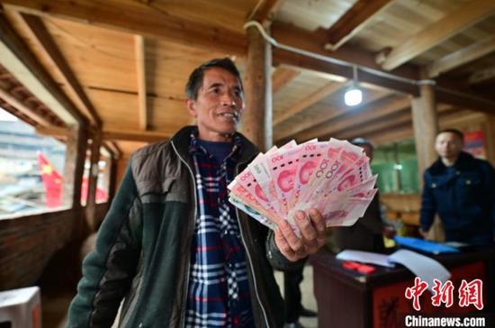 11月27日,在貴州省從江縣斗里鎮臺里村,村民喜領銷售的油茶籽現金?!堑萝?攝