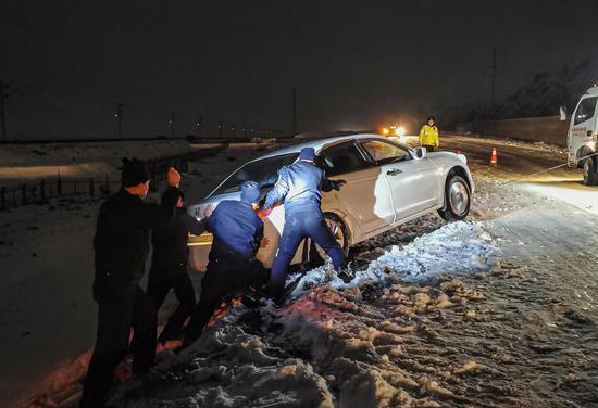 乌兰达布森边境检查站民警合力将事故车辆推出隔离带沟.