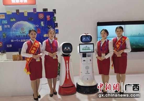 """圖為智能機器人""""工大壯""""和""""工小美""""與禮儀人員一起迎賓。"""