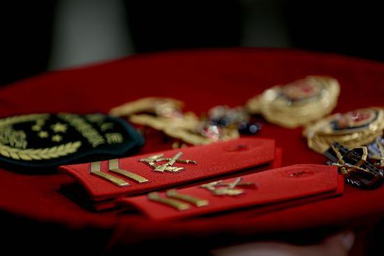 退役士官依依不舍卸下帽徽、領花。 余寧磊 攝