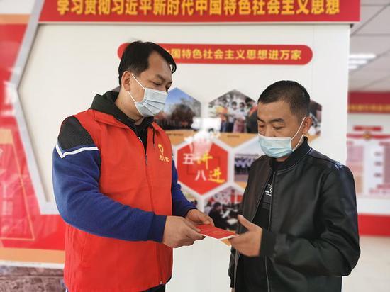 """湖州路东社区""""访惠聚""""工作队副队长王建新给辖区居民宣传宪法,发放《中华人民共和国宪法》手册。"""