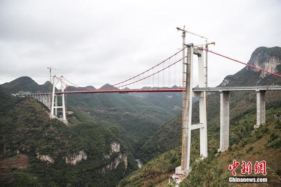 峰林特大桥是兴义环高项目上的特大桥之一,全长1163米,主跨采用550米悬索桥,桥面离谷底364.2米,是中国山区第一座大跨径钢混叠合梁悬索桥。 中新社记者 瞿宏伦 摄