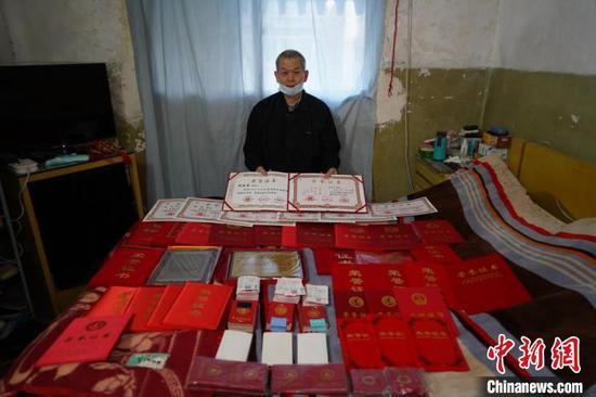 图为杨予军展示全家人的22年来无偿献血证和部分荣誉证书铺满一床。 李超庆 摄