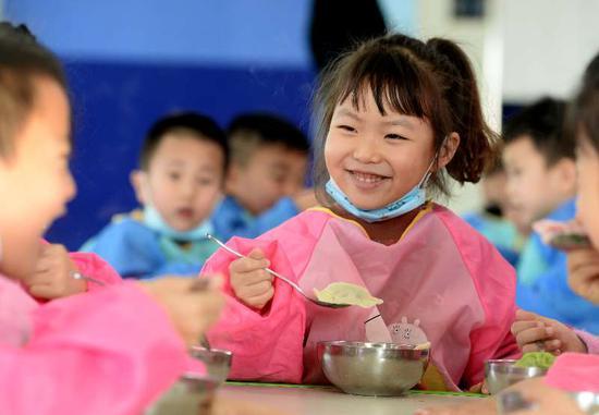12月21日,新疆阿拉尔市塔里木第二幼儿园的孩子们在品尝自己包饺子。