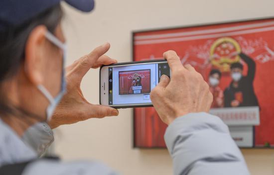 一位参观者在用手机拍摄展出的作品。王刚 摄