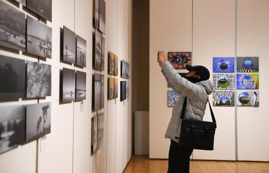 一位参观者在展览现场拍摄作品。王刚 摄