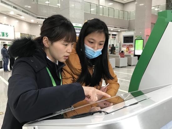 安龙农商银行工作人员引导客户使用智慧柜员机