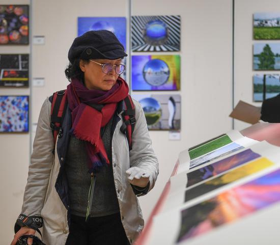 一位参观者被展出的作品所吸引。王刚 摄