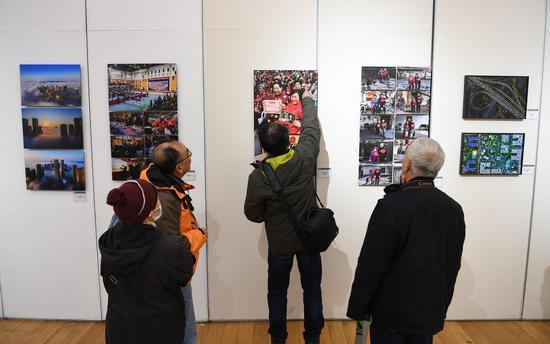 多位参观者在展览现场参观、交流。王刚 摄