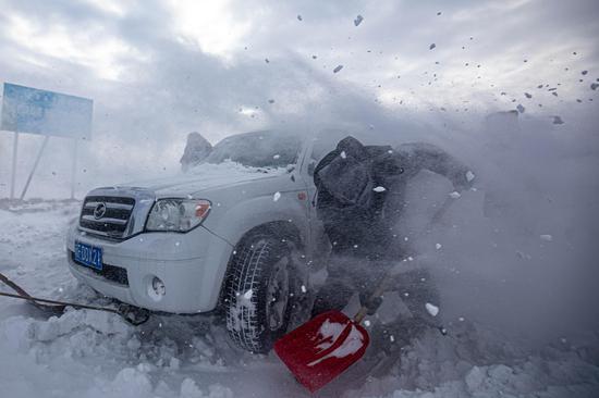 民警为被困车辆铲清积雪。