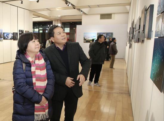 聚星官网省摄协副主席兼秘书长毛小芳(左)与杭州市文联二级巡视员、杭州市摄协主席张友国正在观展。主办方供图