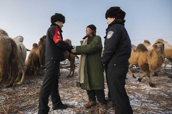 骆驼牧主紧紧握住民警的手表示感谢,谢谢民警为他找回走失的驼群。
