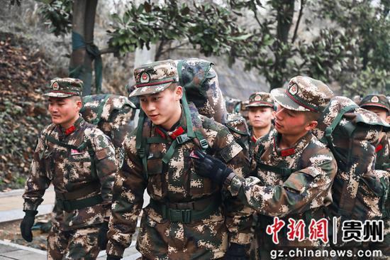 武警贵州总队新训一大队:班长为新兵扶正姓名牌。