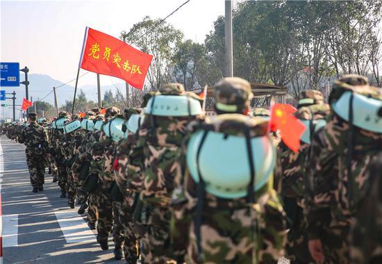 行军队伍中党员突击队旗帜飘扬。 胡港 摄