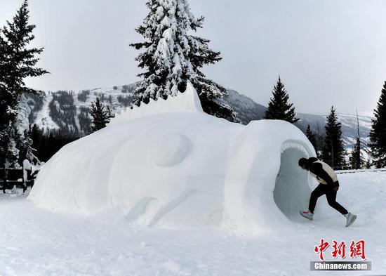 """12月23日,新疆阿勒泰地区喀纳斯景区,游客""""钻进""""巨大的鱼型雪雕口中。据介绍,该雪雕园由多组具有神话色彩的雪雕组成,置身其间如同进入冰雪童话世界。 中新社记者 刘新 摄"""