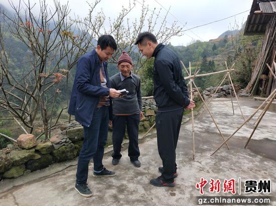金延楷(左一)到背猛村了解當地群眾所思所想,查看群眾存折收入情況,