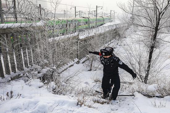 民警踏雪对铁路线路护栏进行安全巡查。