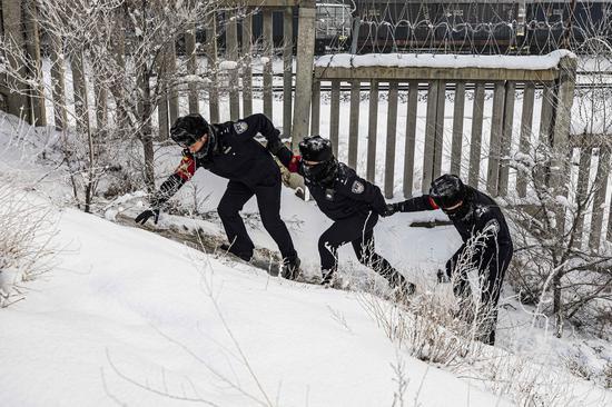 民警踏雪对辖区铁路线路进行安全巡查。