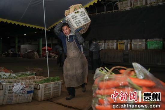 圖為工人將蔬菜從車上搬運到倉庫。 瞿宏倫 攝