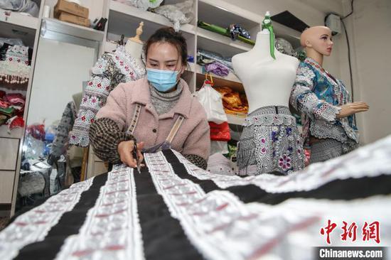 图为一名员工在剪裁苗族服饰配件。 瞿宏伦 摄